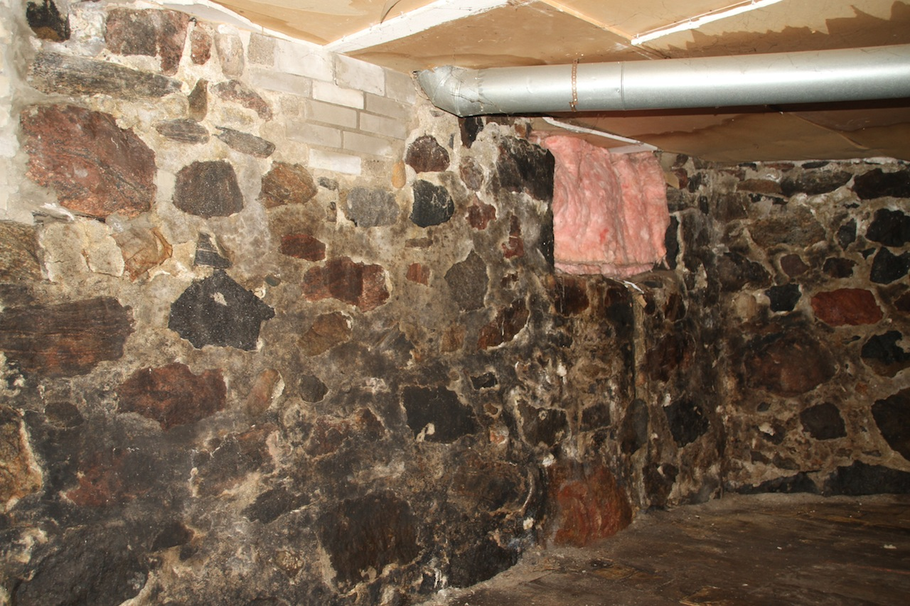 than half of the basement floor is covered with dirt and large stones